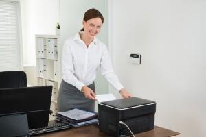 Secretary Inserting Paper In Printer